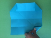 7. Take each corner tab of the entire paper and fold up towards the first point